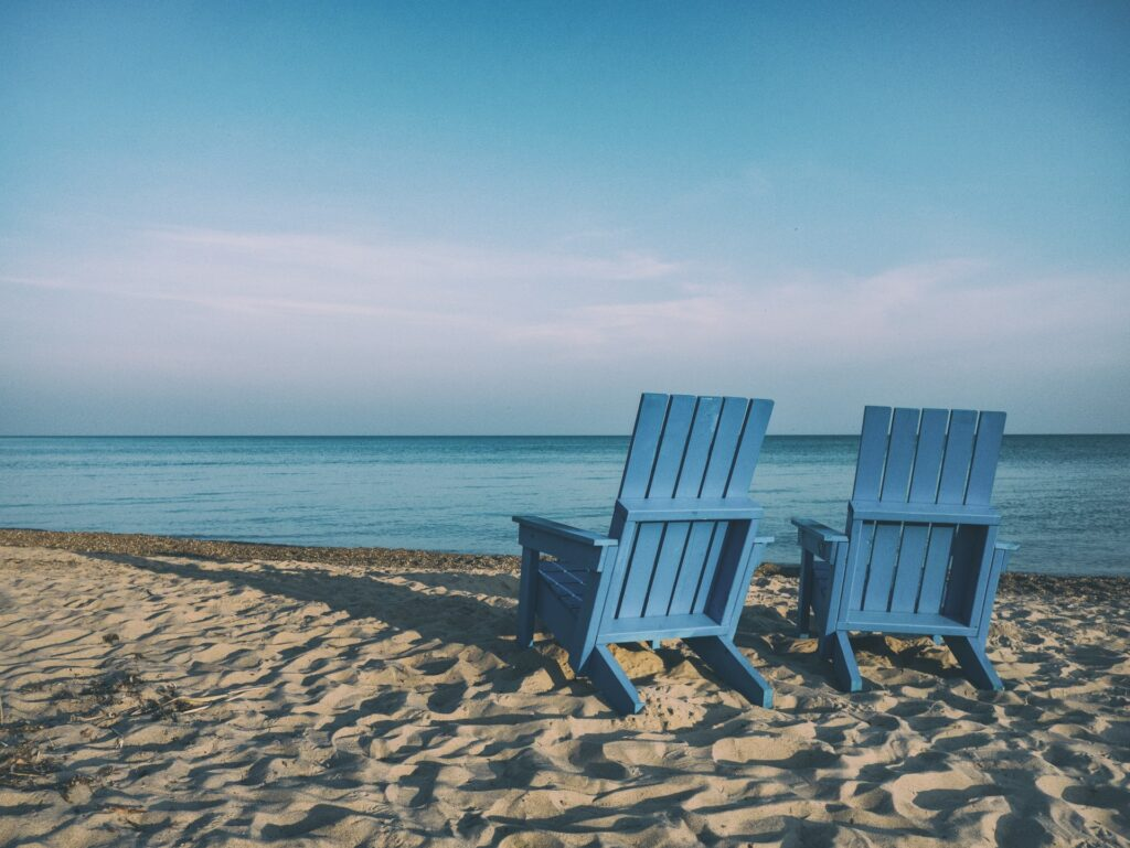 Two blue chairs at beach.